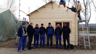 Teilnehmer des Trainingscenters unterstützten beim Aufbau der Holzblockhütten